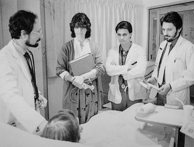 Dr. Joel Deitz teaches residents and medical students from a patient's bedside. c1980-89