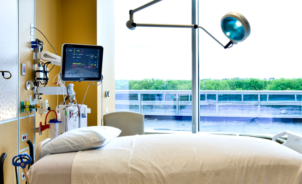 overhead lighting, large-screen cardiac monitor at bedside
